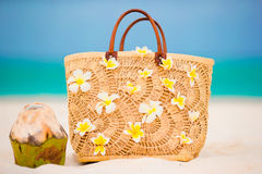 Closeup beautiful bag with frangipani flowers and coconut on white beach Royalty Free Stock Photography