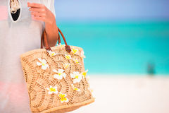 Closeup beautiful bag with frangipani flowers and sunglasses on white beach in female hands Royalty Free Stock Image