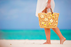 Closeup beautiful bag with frangipani flowers and sunglasses on white beach in female hands Royalty Free Stock Photography