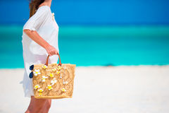 Closeup beautiful bag with frangipani flowers and sunglasses on white beach in female hands Royalty Free Stock Photos