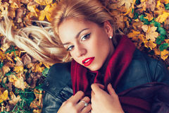 Closeup of beautiful blonde lying in leaves Royalty Free Stock Image