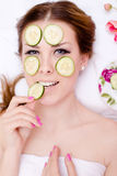 Closeup on beautiful blonde young lady having fun applying slices of cucumber to her face skin & happy smiling. Organic natural spa: closeup portrait of Stock Images