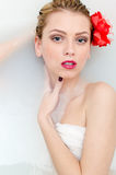 Closeup on beautiful blonde young woman with blue eyes and red lips lying in spa bath with milk and looking at camera Stock Photography