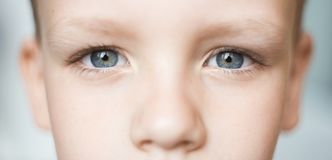 Closeup of beautiful boy eye. Beautiful grey eyes macro shot. Image of a little kid eye open stock photography