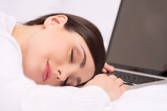 Closeup of beautiful brunette sleeping on desk. Royalty Free Stock Photography