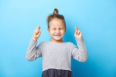 Free Closeup Beautiful Child Girl Crossing Her Fingers, She Squeezed Her Eyes Shut, Has A Hope, Isolated Blue Background. Stock Image - 161659221
