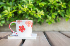 Closeup beautiful cup of coffee on white book on blurred wooden table and green plant in the garden textured background , relaxati. Beautiful cup of coffee on Stock Images