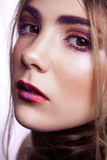 Closeup of beautiful fashion model with makeup and hairstyle on her face. Stock Photo