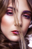 Closeup of beautiful fashion model with makeup and hairstyle on her face. Royalty Free Stock Photo