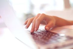 Closeup beautiful female hands typing on keyboard using a laptop in a cafe ,successful business woman,working,,blurred background. Closeup elegant beautiful stock photography