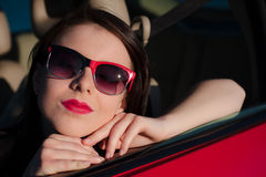 Closeup beautiful female teen with red sunglasses in red car. Closeup of beautiful teen female, in afternoon sun, looking at camera with serious expression.  She Stock Images