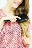 Closeup of beautiful girl brushing long wavy silky blonde hair Royalty Free Stock Photography
