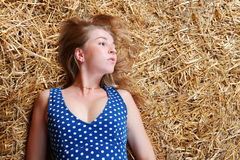Closeup of beautiful girl with long blond hair lying on hay Stock Photo