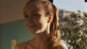 Blond girl with long ponytail stands by flowers stock video