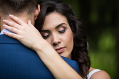 Closeup of a beautiful, happy bride hugging handsome groom with Royalty Free Stock Photo