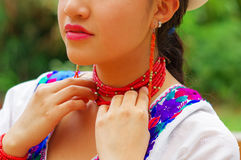 Closeup beautiful hispanic woman wearing traditional andean white blouse with colorful decoration around neck, matching Royalty Free Stock Images