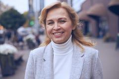 Beautiful mature woman posing on the street Stock Photo