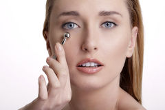 Closeup of beautiful model applying her skin treatment Stock Photography