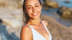 Woman lovely looking at camera with smile and enjoying summer vacation on beach