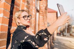 Beautiful cute blonde model in dress posing in the city royalty free stock photos