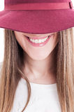 Closeup of beautiful smiling woman face wearing hat and hidding Royalty Free Stock Images