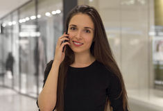Closeup of a beautiful smiling woman using mobile phone. Portrait  a beautiful smiling woman using mobile phone Royalty Free Stock Images