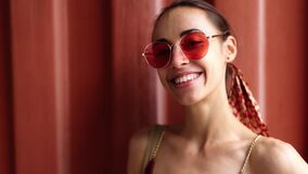 Closeup beautiful smiling young woman in lightweight sundress and pink eyeglasses posing on red wall background