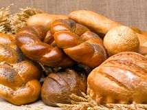 Closeup of a beautiful still-life from bread, pastry products wi. Th wheat ears, poppy seeds and buns on a background of burlap Royalty Free Stock Image