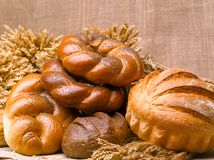 Closeup of a beautiful still-life from bread, pastry products wi. Th wheat ears, poppy seeds and buns on a background of burlap Stock Image