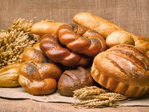 Closeup of a beautiful still-life from bread, pastry products wi. Th wheat ears, poppy seeds and buns on a background of burlap Stock Photo