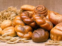 Closeup of a beautiful still-life from bread, pastry products wi. Th wheat ears, poppy seeds and buns on a background of burlap Royalty Free Stock Images