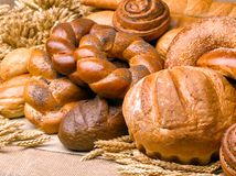 Closeup of a beautiful still-life from bread, pastry products wi. Th wheat ears, poppy seeds and buns. High resolution studio image Stock Photos