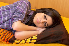 Closeup of beautiful teenage girl lying on bed Royalty Free Stock Photography