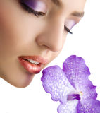 Closeup of beautiful tender female face with violet orchid Royalty Free Stock Photography