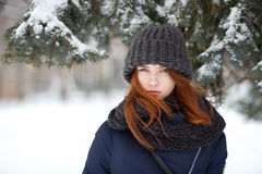 Closeup beautiful winter portrait of young adorable redhead woman in cute knitted hat winter snowy park Royalty Free Stock Images