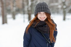 Closeup beautiful winter portrait of young adorable smiling redhead woman in cute knitted hat winter snowy park Royalty Free Stock Photo