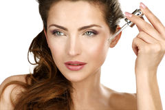 Closeup of a beautiful woman applying a beauty treatment Stock Image
