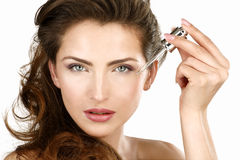 Closeup of a beautiful woman applying a beauty treatment Royalty Free Stock Images