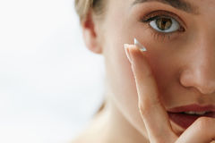 Closeup Of Beautiful Woman Applying Eye Lens In Eye. Eye Care And Contact Lenses For Eyes. Closeup Of Beautiful Woman Face With Smooth Skin And Perfect Makeup Stock Images