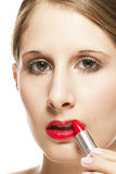 Closeup of a beautiful woman applying lipstick Stock Photo