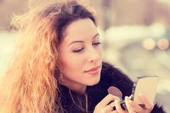Closeup beautiful woman checking her makeup outdoors royalty free stock photo