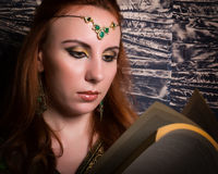 Closeup of Beautiful woman dressed in oriental style with oriental patterns on the hands and face, reading a thick book Royalty Free Stock Image