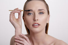 Closeup beautiful woman with eyebrow brush tool Royalty Free Stock Images