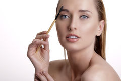 Closeup beautiful woman with eyebrow brush tool Stock Images