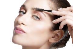 Closeup beautiful woman with eyebrow brush tool Stock Photography