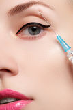 Closeup of beautiful woman gets injection. Beautiful face and the syringe (plastic surgery and cosmetic injection concept). Royalty Free Stock Photo