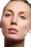 Closeup of beautiful woman gets injection in her face. Full lips. Beautiful face and the syringe plastic surgery and cosmetic Stock Photos