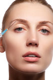 Closeup of beautiful woman gets injection in her face. Full lips. Beautiful face and the syringe plastic surgery and cosmetic Stock Photography