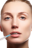 Closeup of beautiful woman gets injection in her lips. Full lips. Beautiful face and the syringe (plastic surgery and cosmetic inj Stock Image