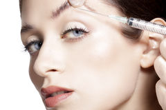 Closeup of beautiful woman gets skin correction injection. On white Stock Photo
